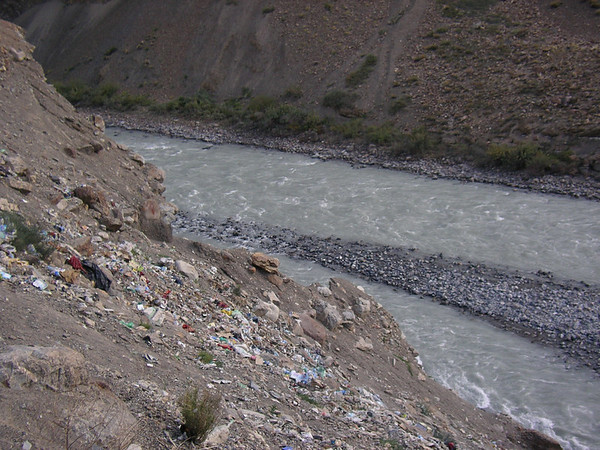 Rubbish tip spilling down onto the Chandra River.